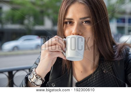 Portrait of a pretty caucasian girl with brown hair drinking coffee on a terrace in the street. She holds the coffee cup with her hand.