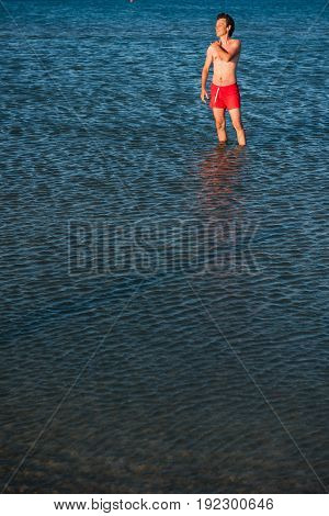 Slim Guy Posing In Red Swimwear In Sea Water