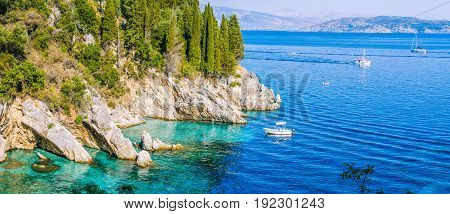 Rocky coastline covered by cypress and tourest boats in azure water, near Kalami, Corfu. Banner