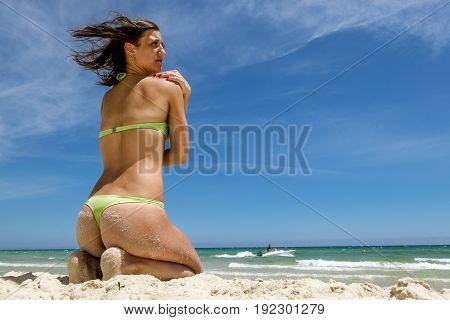 Tanned girl in bikini sitting on the sand on the beach on the Sunny sea coast