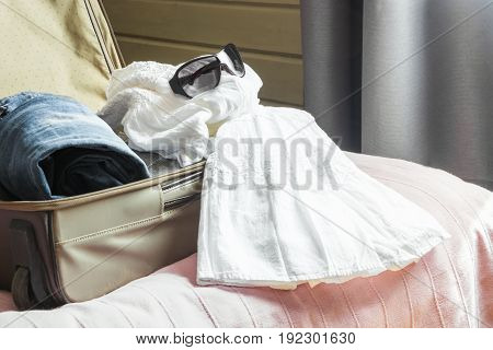 View to the bedroom. Open suitcase with female clothes on the bed.