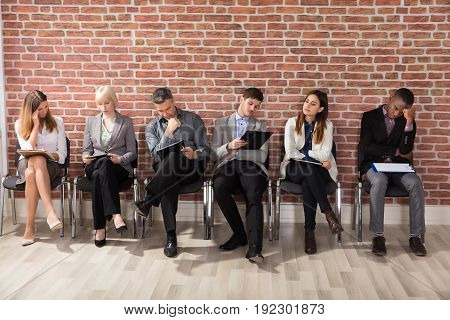Row Of Diverse Professional Applicants Waiting To Be Called For An Interview