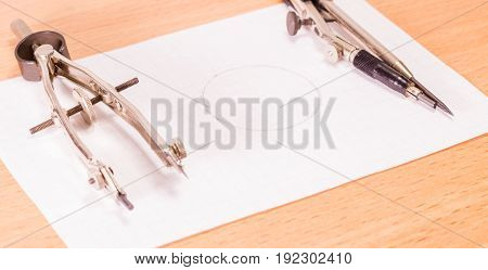 Compasses tool of engineer and student on a sheet of paper with a drawn circle for work and education