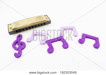 Harmonica with musical figures in violet and glossy tones on a white background.