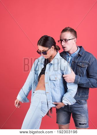 man and girl in sunglasses glasses and jeans jacket on red background denim style beauty and fashion summer couple in love student lifestyle