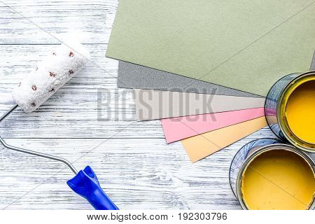 Paints in tin and paint roller on grey wooden desk background top view mock up.