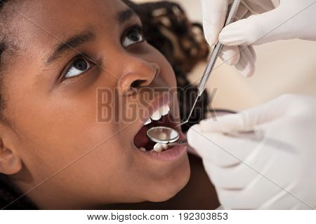 Dentist Examining A African Girls' Teeth In The Clinic