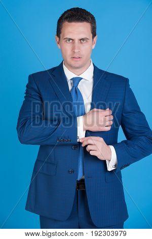 Man In Elegant Formal Suit And Tie Fixing Cufflinks