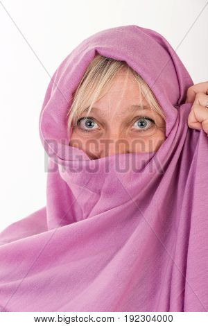 beautiful european mid aged woman hiding her face behind a shawl - studio shot on white background
