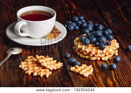 Cup of Tea with Blueberries on the Top of the Belgian Waffles Stack and Other Scattered on Wooden Background.