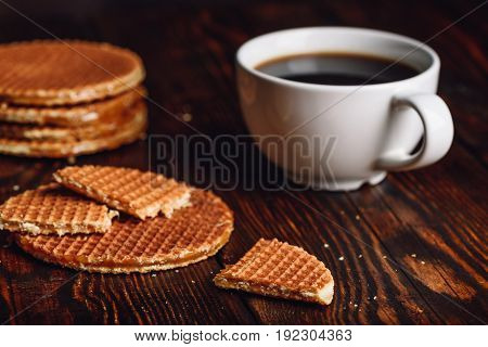 Dutch Waffles with White Cup of Coffee and Waffle Stack on Backdrop.