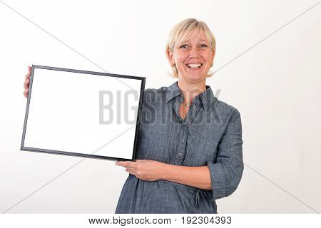 beautiful european mid aged woman in business dress holding a blank white board - studio shot in front of a white background