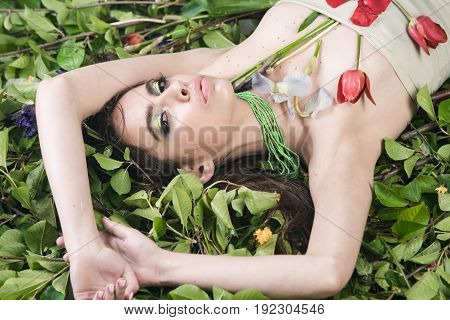 Woman With Fashionable Makeup With Flowers On Green Leaves