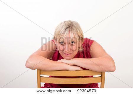 Beautiful european mid aged woman in red dress sitting relaxed on a wooden chair - studio shot in front of a white background