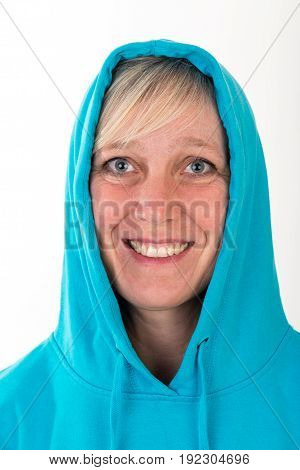 Beautiful european mid aged woman with blonde hair dressed in a light blue casual hooded jacket - studio shot in front of a white background