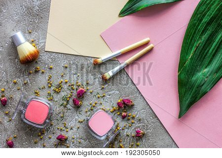 decorative cosmetics design with blusher and make-up brushes on gray table background top view pattern