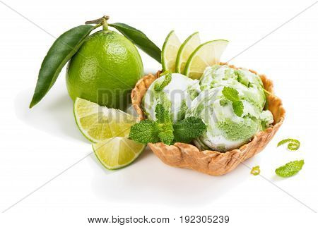 Ice cream of lime in a wafer basket and fresh citrus fruit with green leaves decorated with zest and mint isolated on white background.