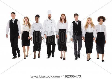 Portrait Of Happy Restaurant Staff Walking Against White Background