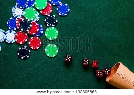Poker chips and dice on a green gaming table top view.
