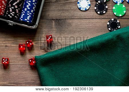 Compulsive gambling. Poker chips and the dice nearby tablet on wooden table top view.