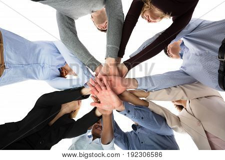 Low Angle View Of College Students Stacking Their Hands Against White Background