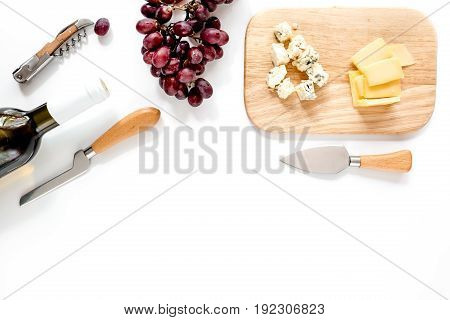 Bottle of red wine with cheese and grape aperitive on white background space for text.