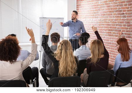 Businesspeople With Hands Raised Answering Businessman In Conference At Office