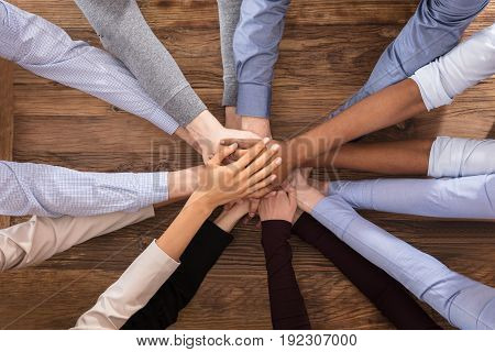 High Angle View Of Multiracial Businesspeople Stacking Their Hands