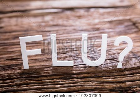 Close-up Of A Flu Text With Question Mark Sign On Wooden Background