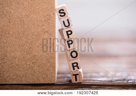 Close-up Of Stacked Support Word On Wooden Cube