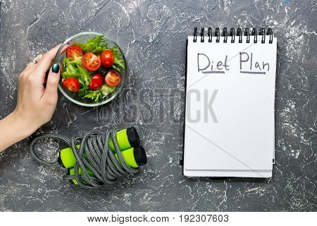 Notebook for diet plan, hand is holding salad with fresh products and jump rope on grey stone table top view.