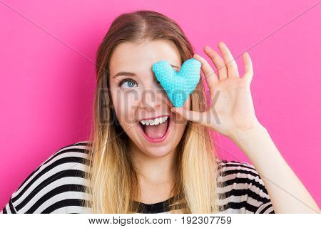 Happy young woman holding a heart cushion on pink background