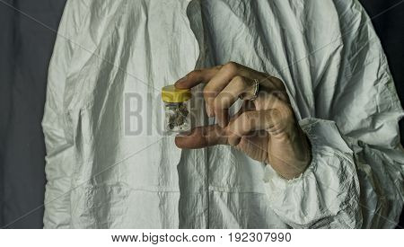 Medical marijuana in transparent and yellow plastic box in hands