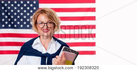Smiling young woman on United States flag background. Student is learning English as a foreign language. American flag.