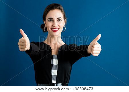 Happy young woman giving thumbs on a dark blue background