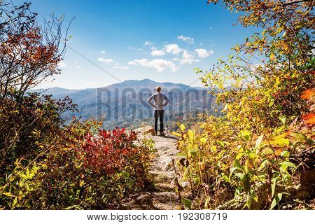 Man at the edge of a cliff overlooking the mountains below