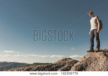 Man walking on the edge of a cliff high above the mountains