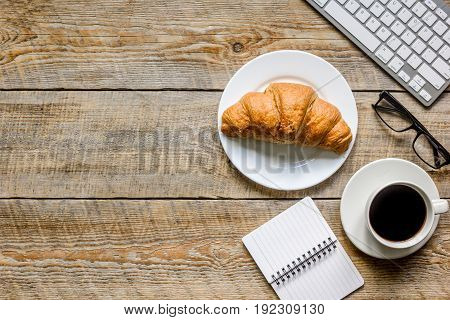 Office lunch of businessman with coffee and croissant, notebook on wooden table background top view space for text