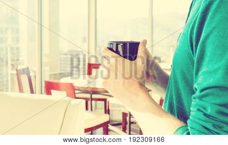 Young man with a cup of coffee in a brightly lit modern interior room