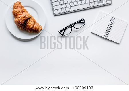 Office lunch of businessman with coffee and croissant, notebook on white table background top view space for text