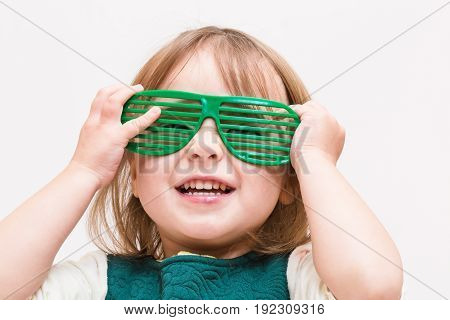 Happy toddler girl wearing shutter shades on a white background
