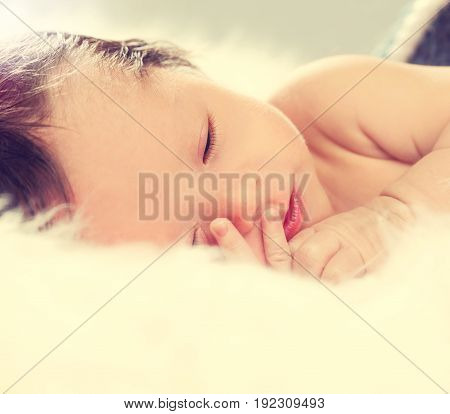 Little baby boy sleeping on a fluffy blanket