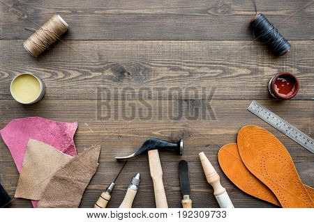 Set of cobbler tools on brown wooden desk background top view copyspace.