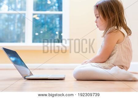 Little girl with her laptop computer at home