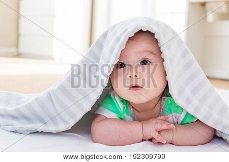 Baby boy under the blanket in his house