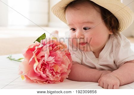 Happy baby boy with a pink flower