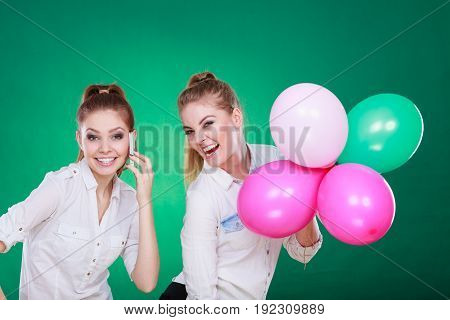 Two Girls With Mobile Phone And Balloons