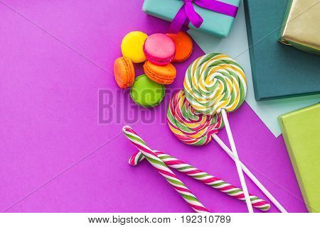 Birthday greeting cards, wrapped gifts and sweets on fuchsia background top view copyspace.