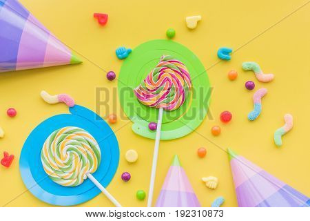Lollipops and party hats for happy birthday on yellow background top view copyspace.