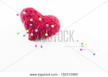 Pillow with nailed pins of different colors and a group scattered to the side on a white background.